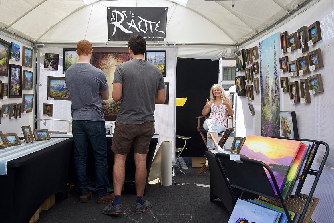 Kalispell artist Raette Merideth gives a thumbs up in her booth featuring her oil landscapes at the Bigfork Festival of the Arts. (Kay Bjork photo)