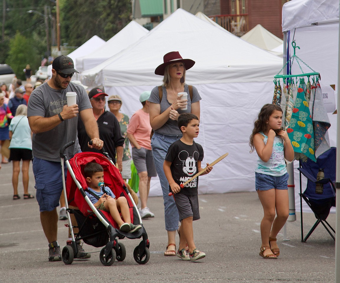 A family drifts through downtown Bigfork while dad and mom enjoy their morning coffee at the Bigfork Festival of the Arts. (Kay Bjork photo)