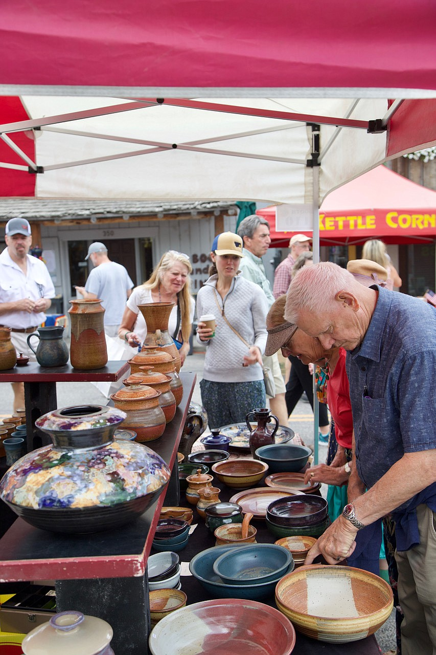 Festival-goers browse through a pottery booth at the Bigfork Festival of the Arts. (Kay Bjork photo)
