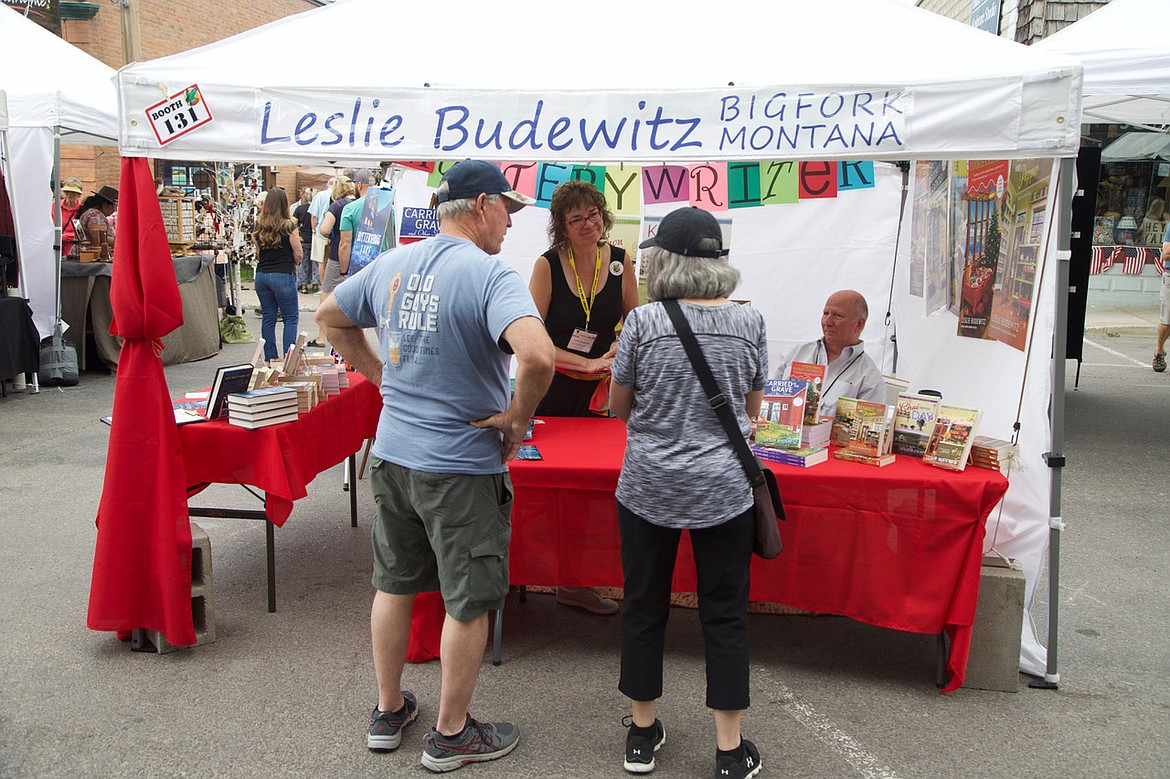 Local mystery writer Leslie Budewitz greets visitors to her booth featuring her locally based books.