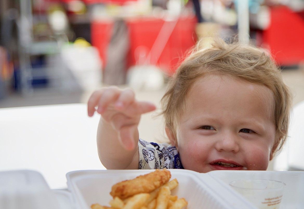 Little Hendrix goes for the fries while enjoying some of the food truck goodies at the Bigfork Festival of the Arts. (Kay Bjork photo)