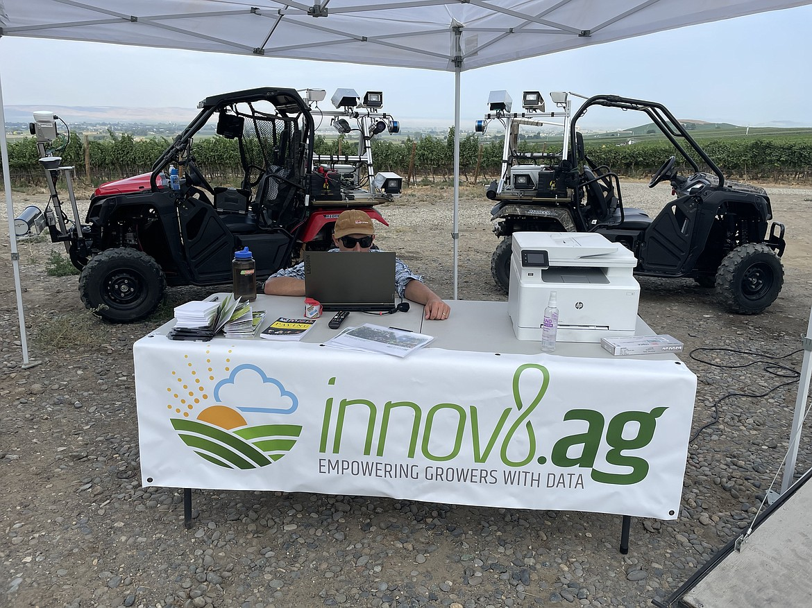 An innov8.ag employee with the company's two souped-up, sensor-packed ATVs, which take pictures and use artificial intelligence to help growers map their orchards and predict their harvest.