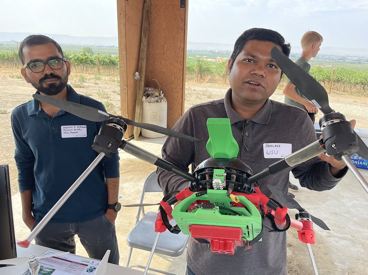 Washington State University researchers Grajanan Kothawade (left) and Abhilash Chamdel (right) show off drones used to take pictures of fields and orchards. Chamdel is holding a custom-built drone that not only takes pictures in visible light, but also in infrared, and can be merged with other data gathered from other field and orchard sensors.