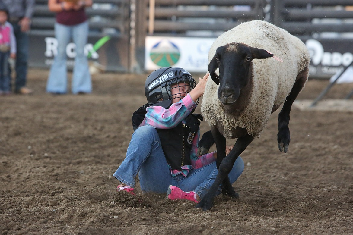Ruby Erickson hits the dirt after getting tossed from her sheep during the Mutton Bustin' event at the beginning of the night on Saturday at the Moses Lake Roundup Rodeo.