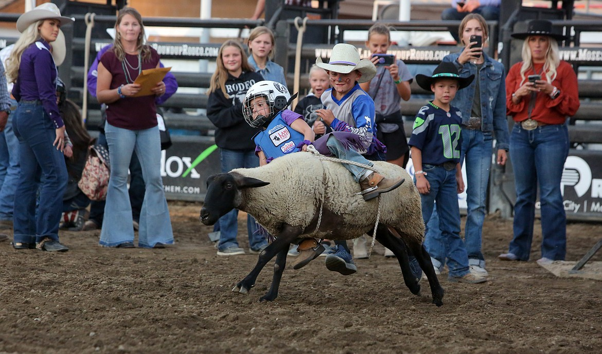 Lila Stacy hangs on to her rope as best she can as her sheep leaves the shoot during the Mutton Bustin' event on Saturday night at the Moses Lake Roundup Rodeo.