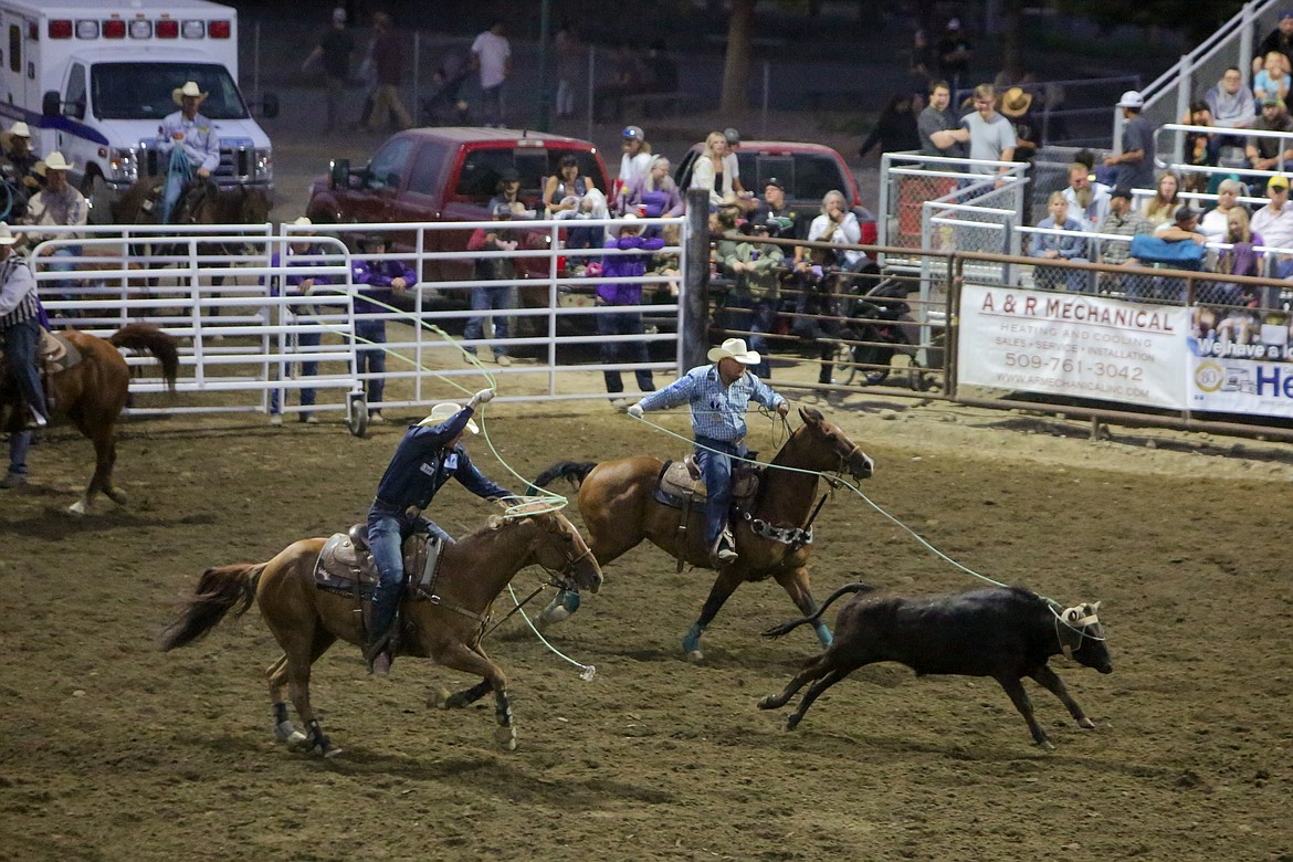 Kellan and Carson Johnson of Casper, Wyoming, compete in the team roping event Saturday night at the Moses Lake Roundup Rodeo.