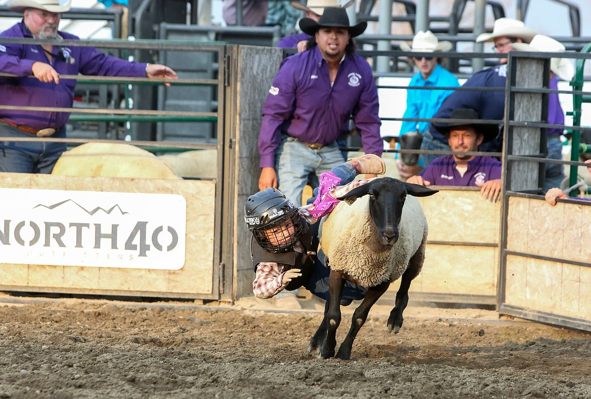 Henry DeBeaumont does his best to hang on to the sheep during the Mutton Bustin' event on Saturday night at the Grant County Fairgrounds.