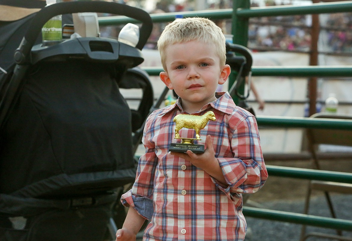 Hunter Ketterer holds up his trophy after taking part in the Mutton Bustin' event at the Moses Lake Roundup Rodeo on Saturday night.