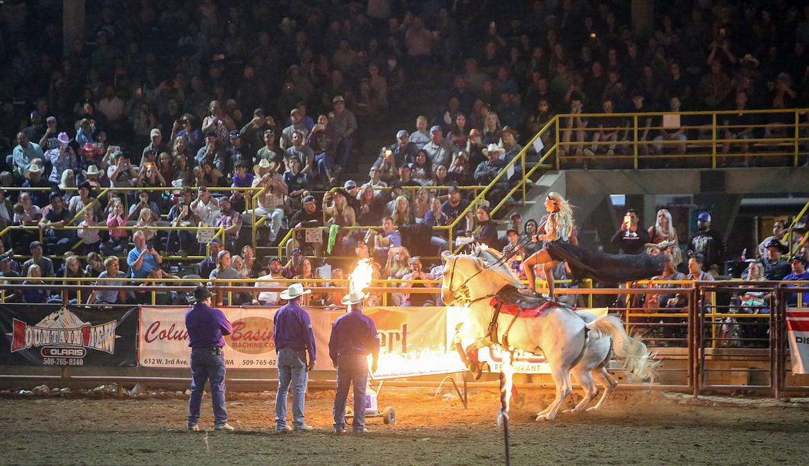 Trick rider Jessica Blair leaps over a flaming barrier while standing on her two horses on Saturday night at the Moses Lake Roundup Rodeo.