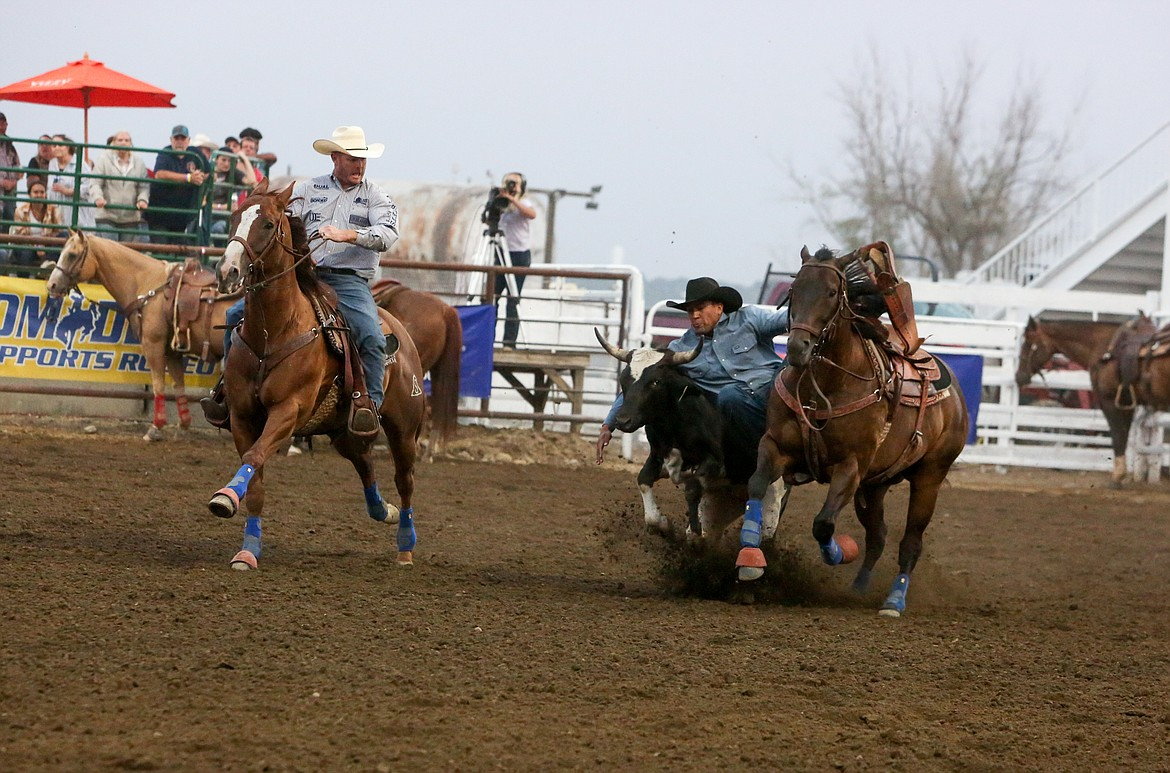 Julius Figeuroa takes the steer to the ground after leaping from his horse in the steer wrestling event Saturday night at the Moses Lake Roundup Rodeo.