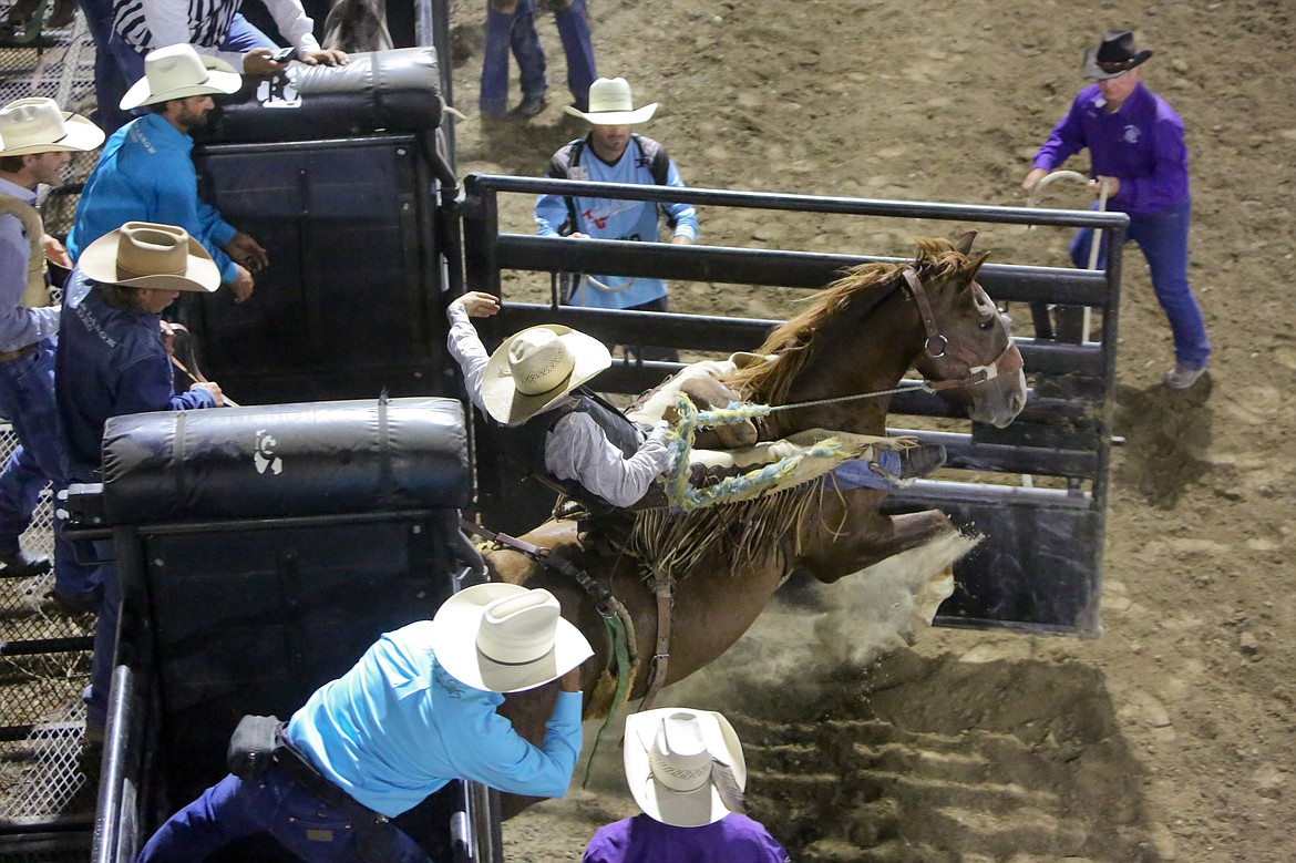 Blaise Freeman hangs on as he leaves the shoot during the saddle bronc riding event Saturday night at the Moses Lake Roundup Rodeo.