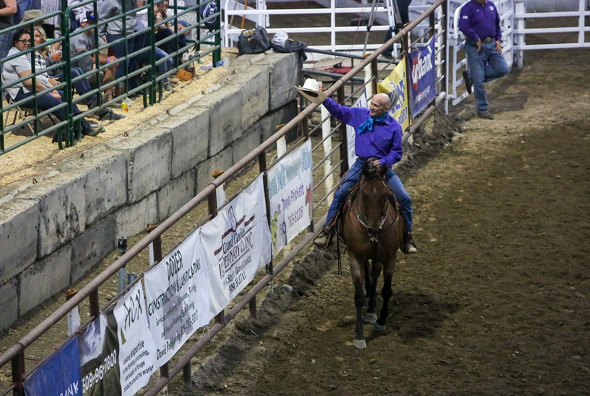 Tom Dent of Moses Lake waves his hat to the crowd as he's honored as the Moses Lake Roundup Rodeo Man of the Year on Saturday night.