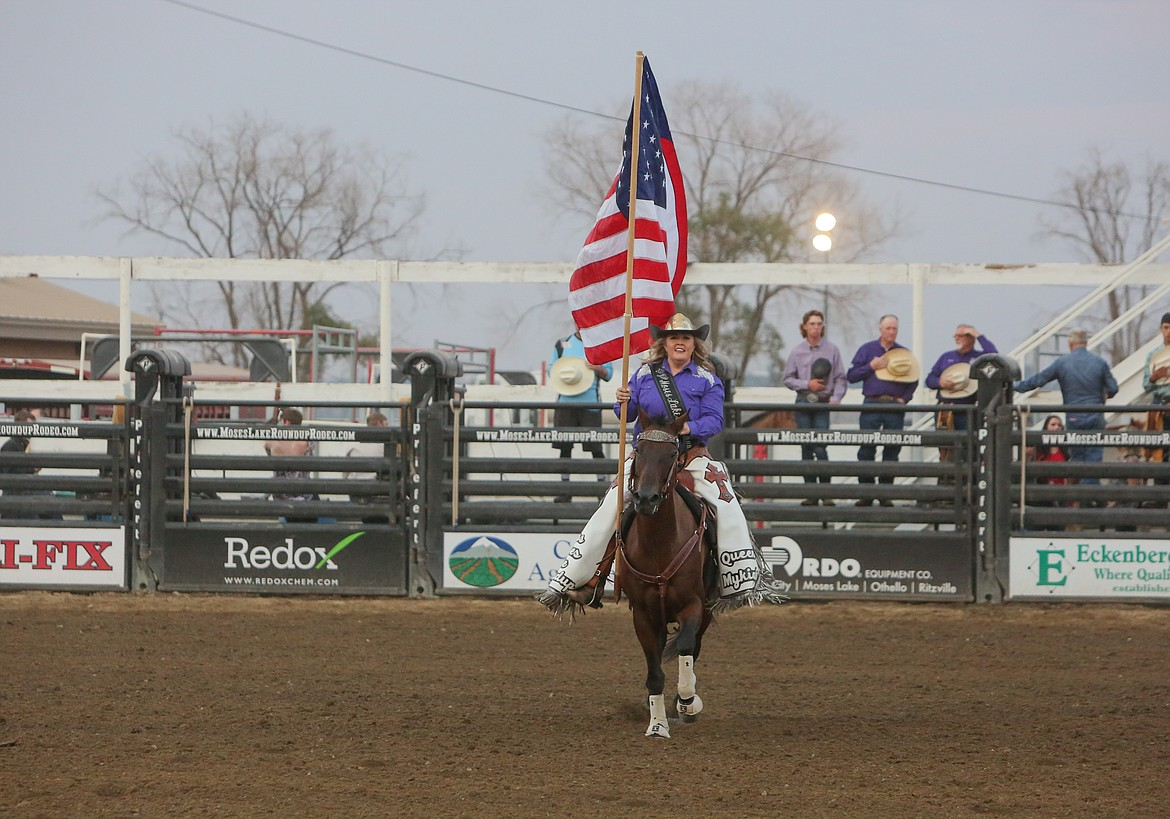 Moses Lake Roundup Queen Mykiah Hollenbeck brings the flag out into the middle of the arena before the national anthem on Saturday night at the Moses Lake Roundup.