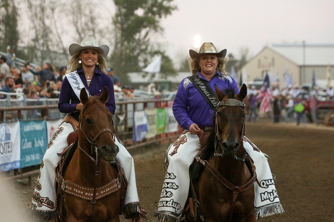 Miss Teen Rodeo Washington Chloe Brown, left, and Moses Lake Roundup Queen Mykiah Hollenbeck make their way around the arena on Saturday night at the Moses Lake Roundup.