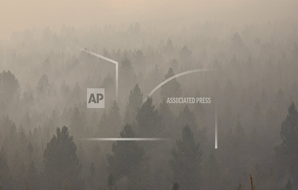 In this Aug. 11, 2021 file photo smoke from a wildfire obscures a stand of trees on the Northern Cheyenne Indian Reservation, near Ashland, Mont. In southeastern Montana, communities in and around the Northern Cheyenne Indian Reservation were ordered to evacuate as the Richard Spring Fire grew amid erratic winds. (AP Photo/Matthew Brown,File)