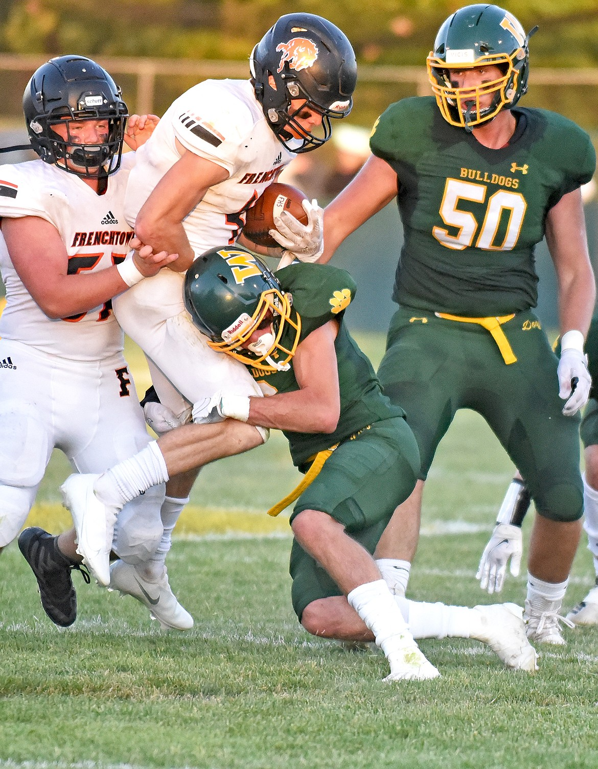 Bulldog Bodie Smith makes a defensive tackle against Frenchtown with support from teammate Talon Holmquist in a game on Friday in Whitefish. (Whitney England/Whitefish Pilot)