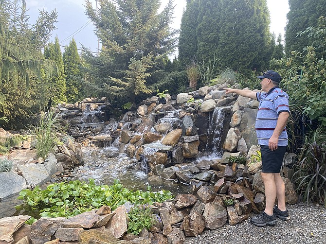 Roosevelt Inn owner John Hough looks over his handiwork, an extravagant waterfall feature that Hough designed and built with 22 tons of rock placed by hand.