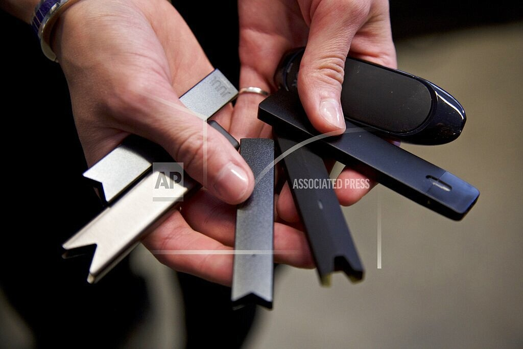 In this April 16, 2019 file photo, a researcher holds vape pens in a laboratory in Portland, Ore. On Thursday, Sept. 9, 2021, U.S. health officials delayed a high-stakes decision on whether to permit best selling vaping brand Juul to stay on the market, while ordering thousands of other electronic cigarettes off store shelves. (AP Photo/Craig Mitchelldyer, File)