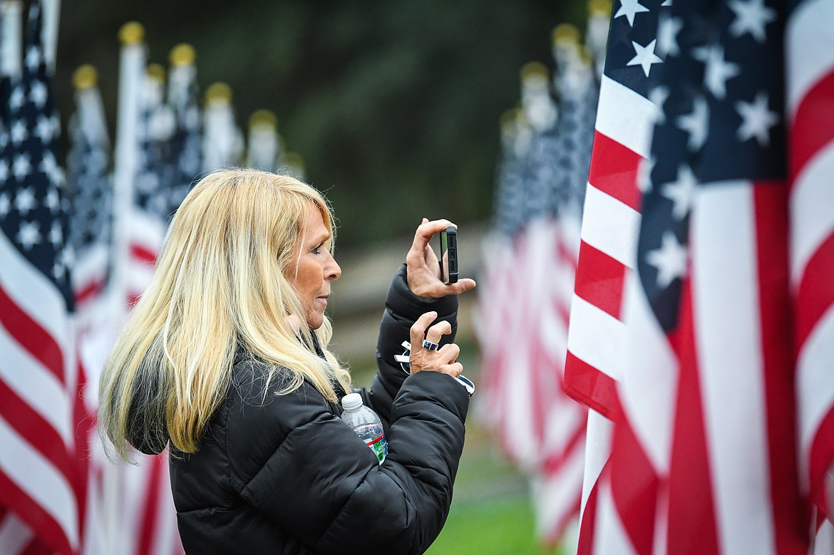 Molly Linn, of Bigfork, takes photographs at the Field of Honor after the 9/11 Honor & Serve Foundation's 20-year Remembrance Ceremony at Wrangler Springs Ranch in Bigfork on Saturday, Sept. 11, 2021. (Casey Kreider/Daily Inter Lake)