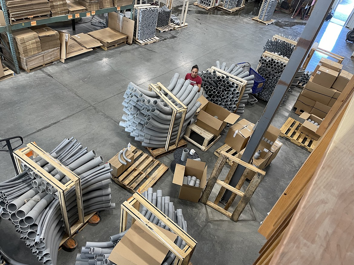 Raceways employee Karla Negrete stacks and moves curved sections of pipe known as sweeps in the company's new Quincy factory.