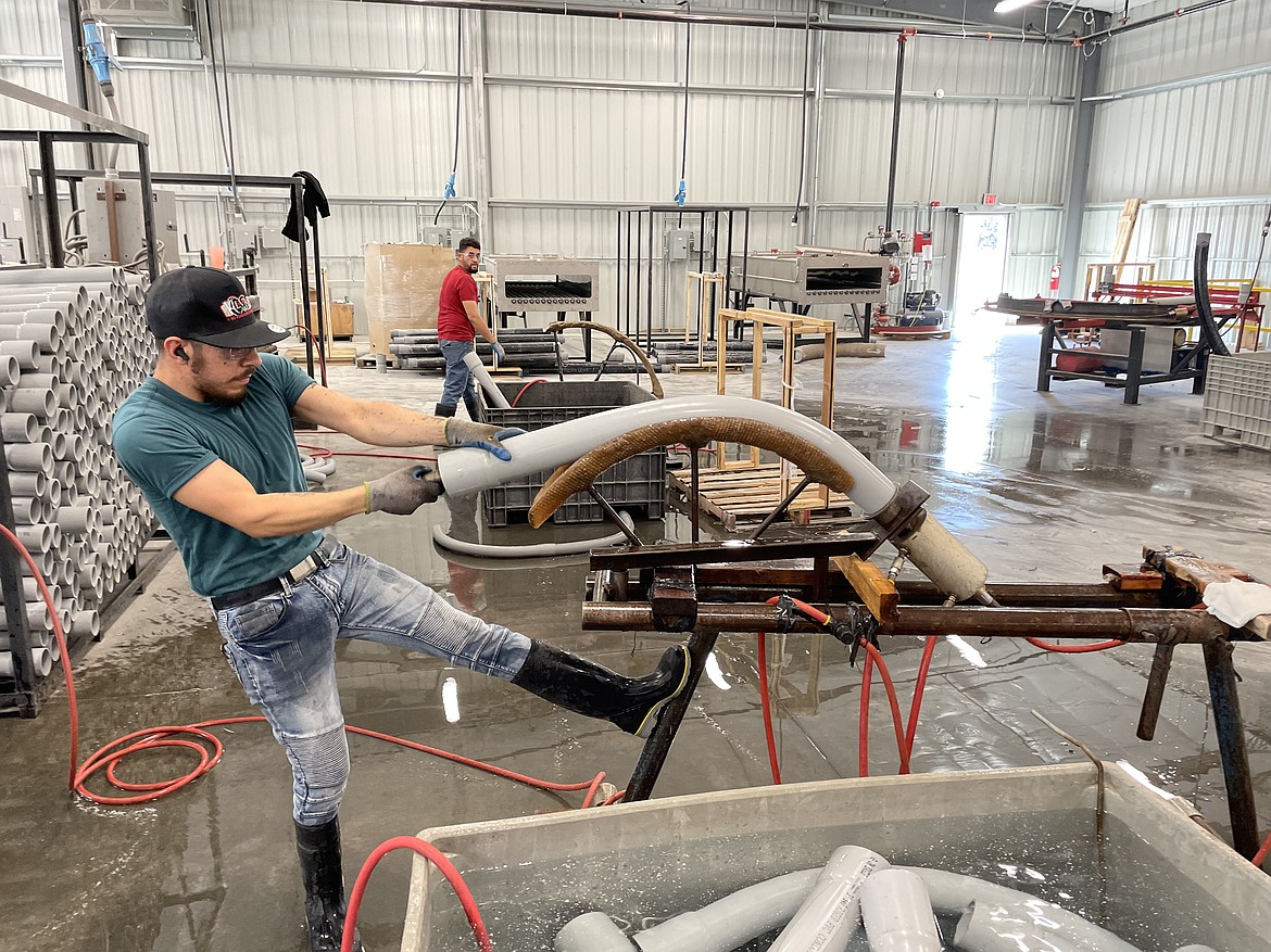A Raceways Technology employee shows how a large PVC pipe is bent.