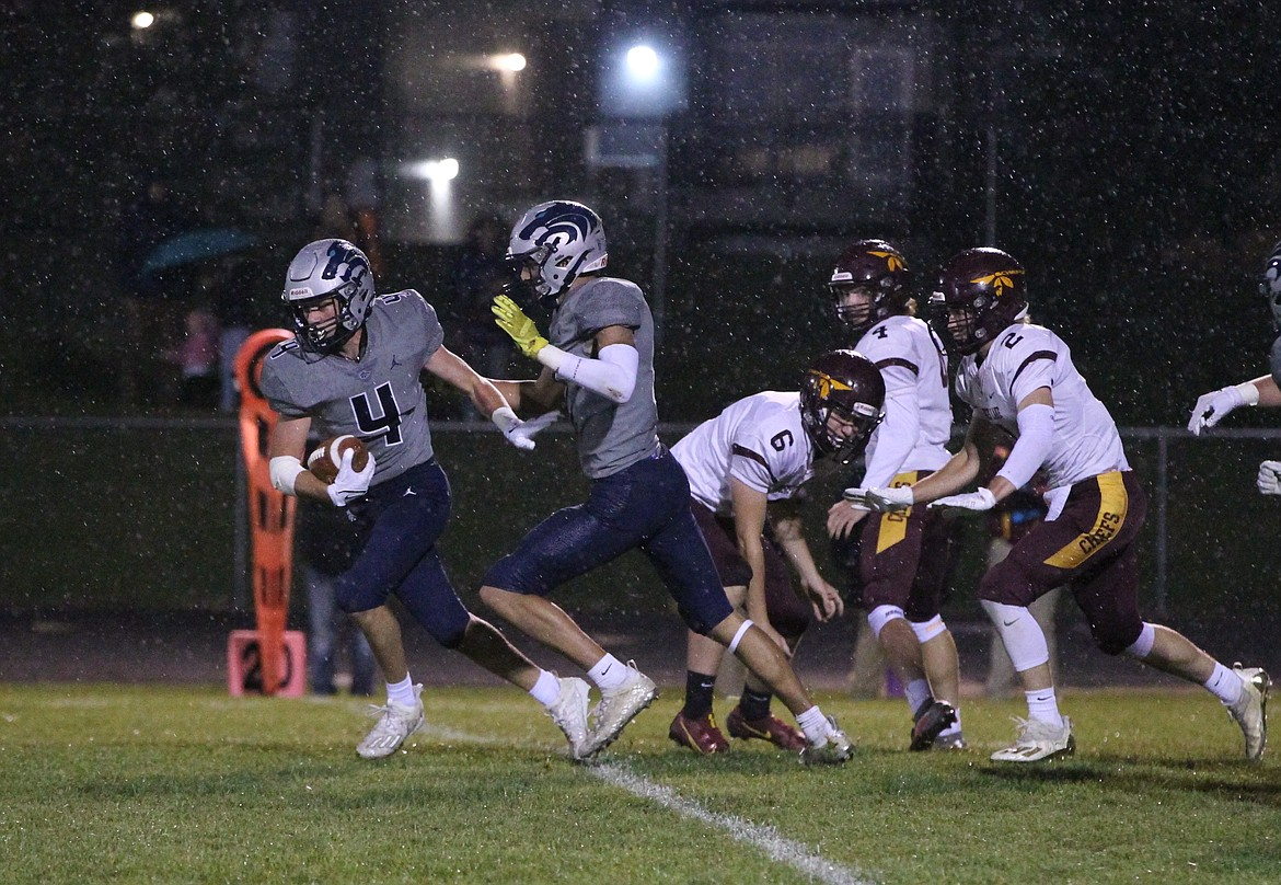 MARK NELKE/Press Eric Bumbaugh (4) of Lake City heads for the end zone after picking up an fumbled snap from center on a Moses Lake field goal attempt late in the first half Friday night. Also pictured is Wayne Queen of Lake City, and holder Gavin Reyer (6), kicker Iden Bone (4) and Asher Lindgren (2) of Moses Lake.