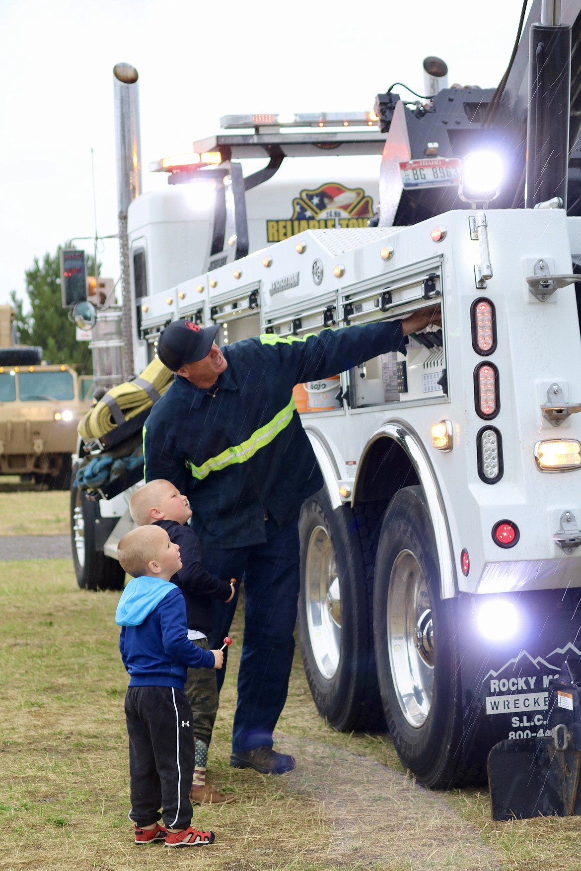Tow truck operator Joe Andrews shows brothers Kade, 3, front, and Logan Abey, 4, how to operate the machine at Meet the Machines at the Kootenai County Fairgrounds on Saturday morning. HANNAH NEFF/Press
