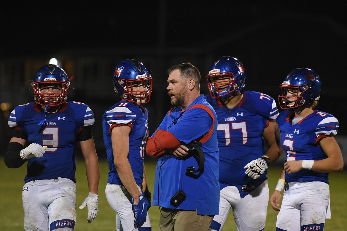 Bigfork head football coach Jim Benn consults with his team during a timeout late in the fourth quarter against Jefferson Friday. (Jeremy Weber/Bigfork Eagle)