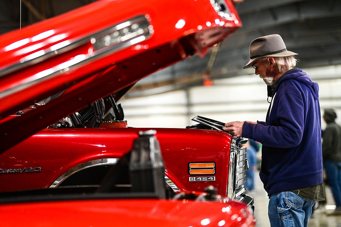 Larry Barrow pages through a booklet about a 1971 Chevy K20 truck owned by Kevin McRae of Kalispell at the Glacier Street Rod Association's 40th annual car show at the Flathead County Fairgrounds on Saturday, Oct. 9. (Casey Kreider/Daily Inter Lake)